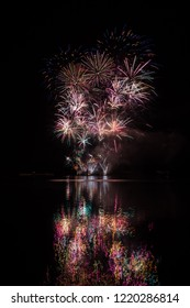 Big crackling explosion in rich fireworks over Brno's Dam with lake reflection