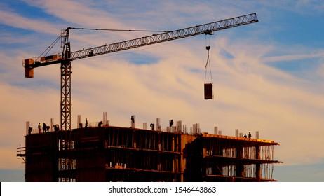 Big crane, block of flats and sunset sky, urban development