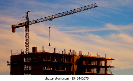 Big crane silhouette and many workers building new construction under a beautiful colorful sunset sky