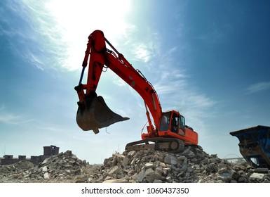 Big crawler excavator at work on demolition construction site in daytime.