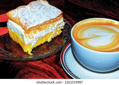 Big creamy home made cake served with caffe latte in popular cafeteria in Ptuj, Slovenia.