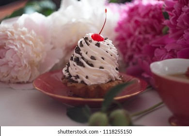 big creamy white cake with cherry and chocolate on a red plate and pink and white peones
