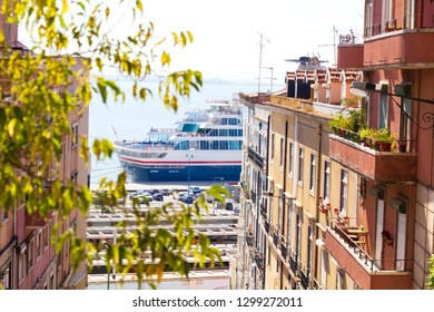 Big cruise ship on Tagus river visible between two beautiful downtown buildings with bright facades in Lisbon, Portugal.