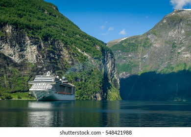 Big cruising ship at beautiful norwegian fjord with steep shores. Geiranger fjord, Norway.