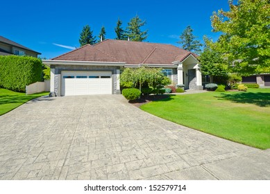 Big custom made double doors garage with nicely paved long driveway and trimmed bushes aside in the suburbs of Vancouver, Canada.