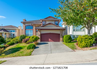 Big custom made house with nicely landscaped and trimmed front yard and driveway to garage in the suburbs of Vancouver, Canada.
