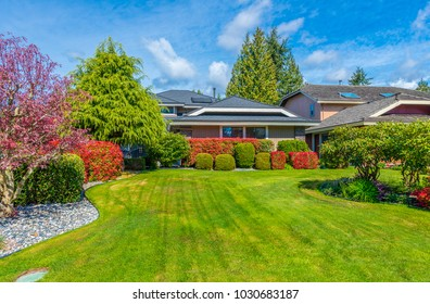 Big custom made luxury house with nicely landscaped and trimmed front yard.