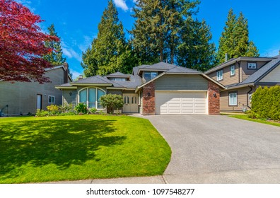 Big custom made luxury house with nicely landscaped and trimmed front yard in the suburbs of Vancouver, Canada.