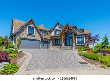 Big custom made luxury house with nicely landscaped and trimmed front yard and driveway to garage in the suburbs of Vancouver, Canada.