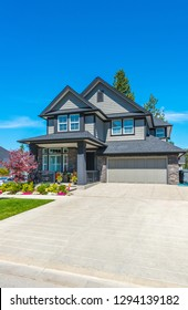 Big custom made luxury house with nicely landscaped front yard and driveway to the garage.