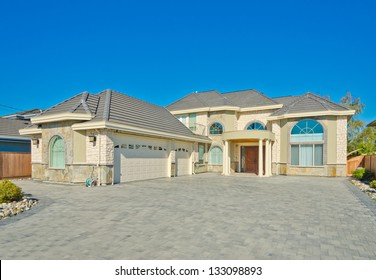 Big custom made luxury house with nicely paved driveway and triple doors garage in the suburbs of Vancouver, Canada.