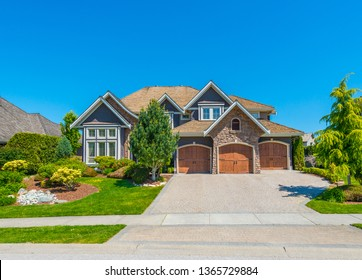 Big custom made luxury house with nicely landscaped and trimmed front yard and driveway to garage.