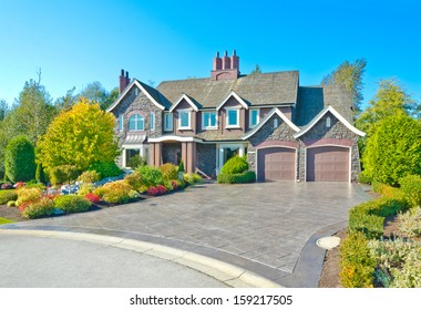 Big custom made luxury house with nicely trimmed and landscaped front yard, two doors garage and long and wide paved driveway in the suburbs of Vancouver, Canada.