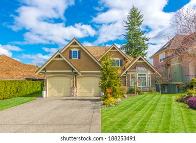 Big custom made luxury house with double doors garage, long and wide driveway and nicely trimmed and landscaped front yard in the suburbs of Vancouver, Canada.