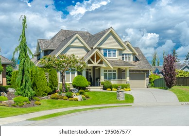 Big custom made luxury house with nicely landscaped front yard and long and wide driveway to garage in the suburb of Vancouver, Canada.