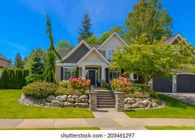Big custom made luxury house with nicely trimmed and  landscaped front yard and steps and stones to the entrance  in the suburb of Vancouver, Canada.