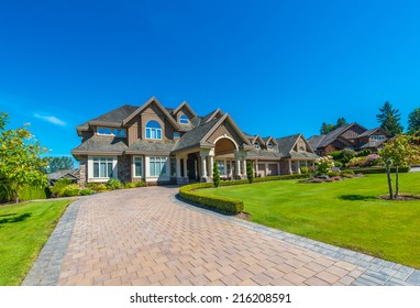 Big custom made luxury house with nicely landscaped front yard and paved driveway to garage in the suburbs of Vancouver, Canada.
