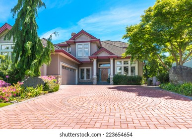 Big custom made luxury house with nicely paved front yard and long and wide driveway to garage in the suburb of Vancouver, Canada.