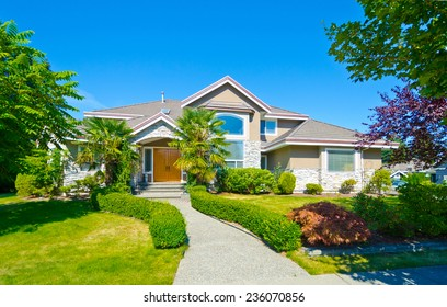 Big custom made luxury house with nicely landscaped and trimmed front yard and long doorway in the suburbs of Vancouver, Canada.