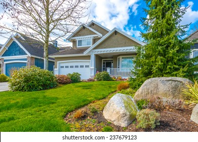 Big custom made luxury house with nicely landscaped front yard and double doors garage in the suburbs of Vancouver, Canada.