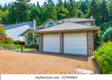Big custom made luxury house with nicely landscaped and trimmed front yard and paved driveway to garage in the suburbs of Vancouver, Canada.