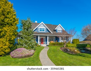 Big custom made luxury house with nicely landscaped and trimmed front yard and doorway in the suburbs of Vancouver, Canada.