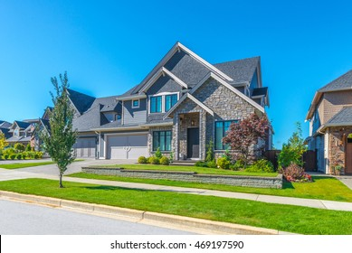Big custom made luxury house with nicely landscaped front yard and driveway to garage in the suburbs of Vancouver, Canada.