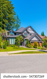 Big custom made luxury house with nicely landscaped front yard in the suburbs of Vancouver, Canada.