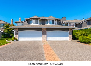 Big custom made luxury house, duplex with nicely trimmed and landscaped front yard and driveway to garage in the suburbs of Vancouver, Canada.