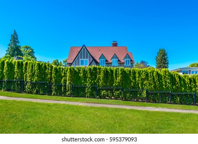 Big custom made luxury house behind the nicely trimmed bushes, green fence in the suburbs of Vancouver, Canada.
