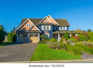 Big custom made luxury house at fall, autumn season, time with nicely landscaped and trimmed front yard in the suburbs of Vancouver, Canada.