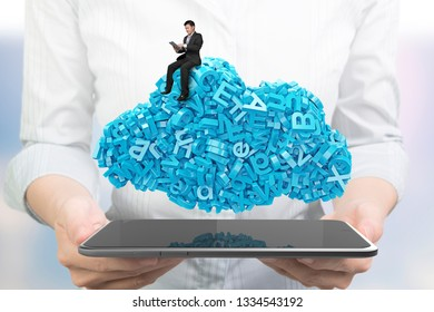 Big data and cloud computing concept. Woman hands holding digital tablet with working businessman sitting on cloud of blue letters and numbers, front view.