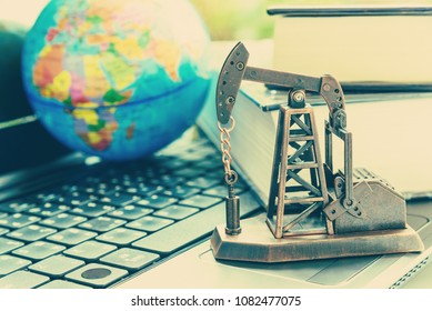 Big data and data mining concept : Oil or petroleum pump jack on two thick books, depicts the collective data or extraction technic that are performed on large sets / volume of data, uncovering info.
