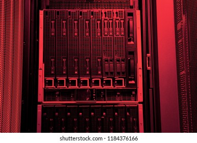 Big data server cloud hardware in red light close-up in series of mainframes in modern data center. Red tone