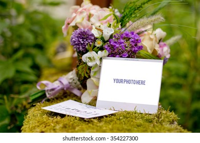 "The big day concept focused on invitation card with ""your text here"", in background natural bouquet of wild flowers, on moss and with trees in background"