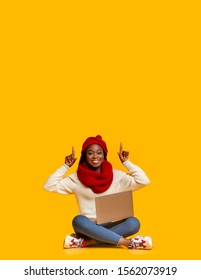Big deal. Excited afro winter girl with laptop sitting on floor and pointing up at empty space, yellow studio background
