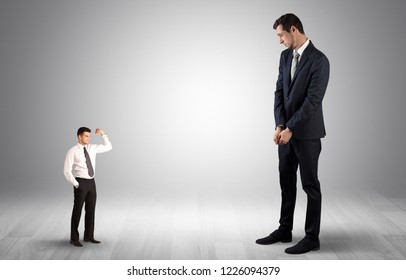 Big debutant young businessman scared of small strong businessman