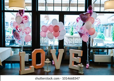 Big decorated letters Love and inflatable pink and white balls with helium are on a wooden floor in a restaurant in the area for the wedding ceremony. Photo Zone on day of lovers and valentines day.