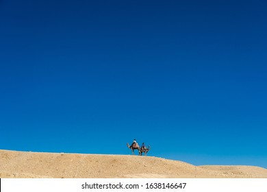 Big Desert Landscape and Very Small People on Camels with Deep Blue Sky in Egypt