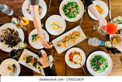 Big Dinner Table of People Eating Drinking Together