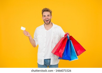 Big discount. Great choices great purchases. Happy man holding purchases in paper bags. Cheerful client customer consumer smiling with fashion purchases. Impulse purchases. Consumerism concept.