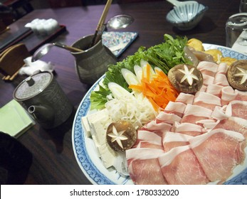 Big Dish with thin pork meat slices, fresh vegetables and mushrooms, traditional japanese shabu shabu soup ingredients ready for cooking