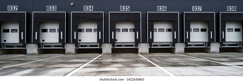 Big distribution warehouse with industrial doors for loading dock trucks - wide banner