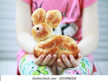 Big dough bunny  in the hands of a child, freshly baked for easter holidays, Baking with kids. Selective focus