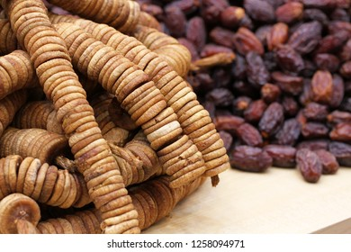Big dried dates and dried figs strung on twine, lying on a large counter at the market in Deira, Dubai