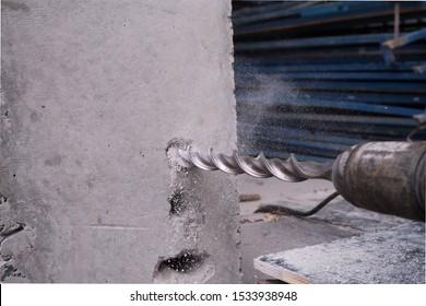 Big drill bit in hole of column concrete closeup.