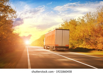 A big driving fast truck with a red trailer and other cars on a countryside road with autumn trees against a blue sky with a sunset
