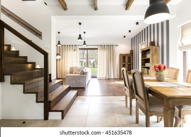 Big elegant house with spacious dining hall and wooden stairs on the first floor. In the background bright living room