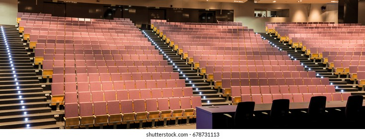 Big empty elegant lecture hall with red chairs on new contemporary college university