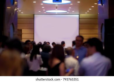 big empty screen over people in meeting room